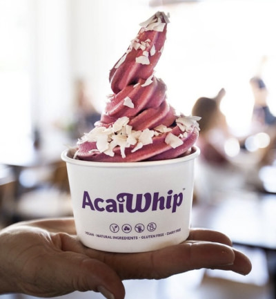 An image of a takeaway acaiwhip with coconut flakes ontop