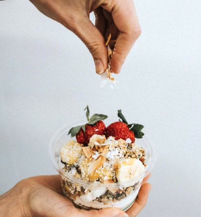 An image of a hand garnishing coconut flakes over a Cocowhip cup