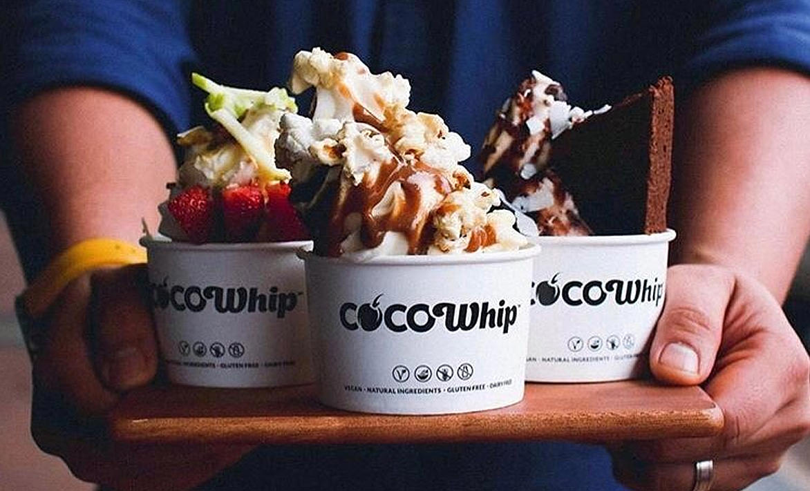 Three cocowhips on a tray with toppings