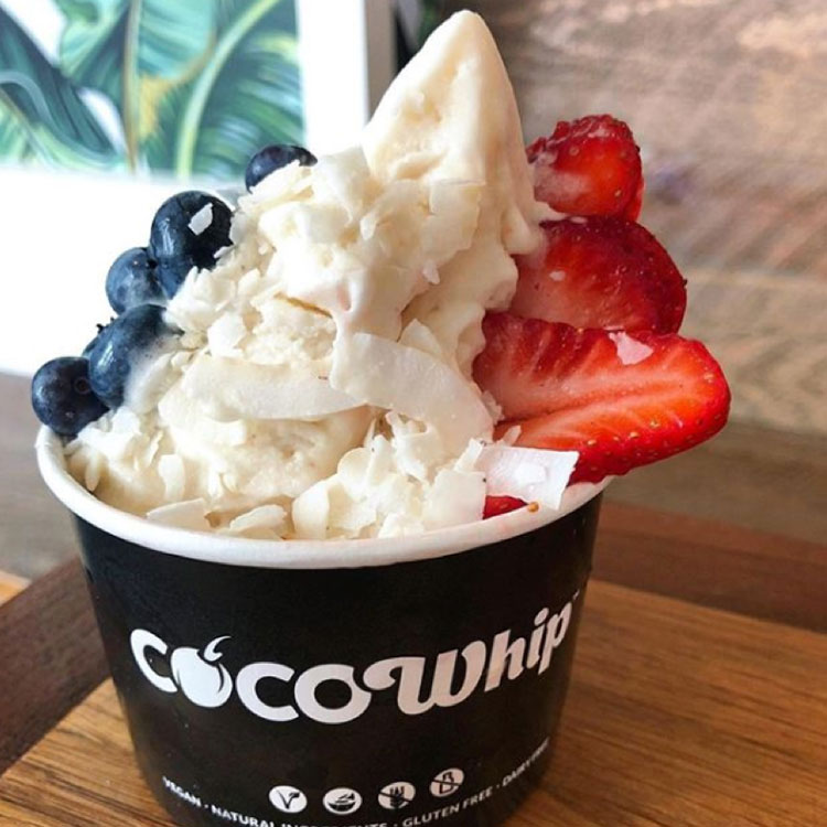 Cup of Cocowhip topped with blueberries, strawberries and coconut